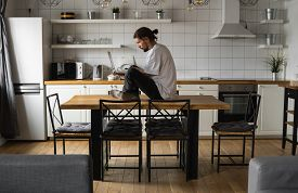 Freelancer Working From Home Sitting On A Top Of The Kitchen Table And Using Laptop. Bearded Man Wor