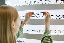 Woman Pick A Eyeglasses From Shelf In Optics Store