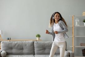 Overjoyed Young Woman Listen To Music Dancing At Home