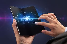 Businessman holding a foldable smartphone with CYBER INSURANCE inscription, cyber security concept