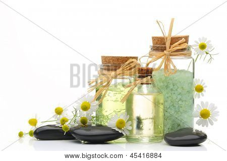Spa still life with sea salt,cosmetic oil and zen stone on white background.