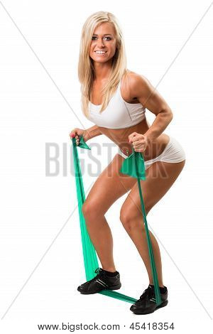 Lovely woman doing fitness exercises with rubber band
