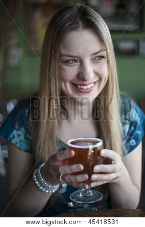 Blonde Woman With Beautiful Blue Eyes Drinks A Goblet Of Beer