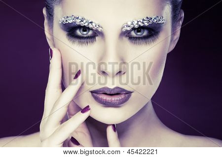 Portrait of sexual beautiful girl with strasses on face, on a violet background poster