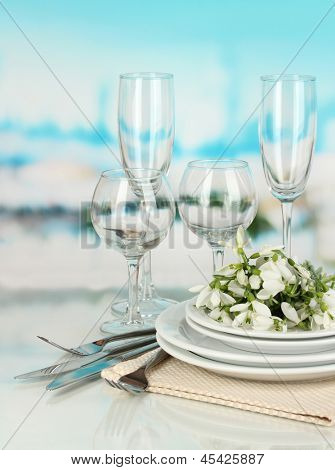 Serving dishes and snowdrops on blue natural background