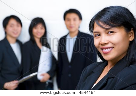 Young Asian Businesswoman Smiling To Camera With Other People On Background