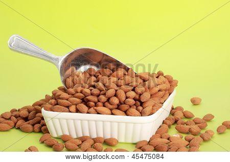 nice metallic scoop of fresh unshelled almonds poster