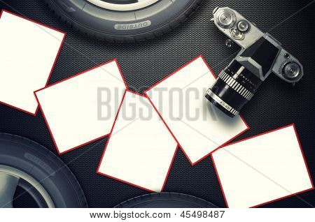 Blank card and vintage camera with car tire on carbon fiber background.