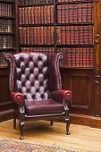 Traditional Chesterfield chair in classical library room poster