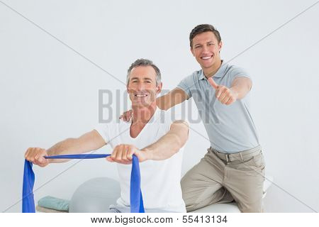 Male therapist massaging a mans shoulder while gesturing thumbs up in the gym at hospital