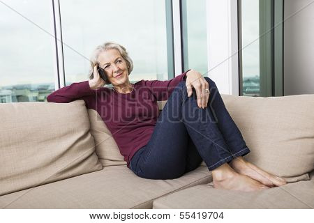 Full-length of senior woman answering smart phone on sofa at home