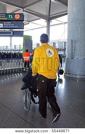 Porter pushing wheelchair at airport.
