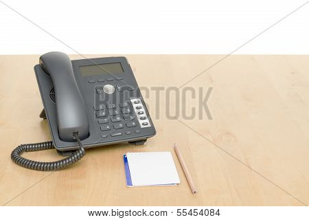 Phone On Desk With Notepad On Wooden Desk
