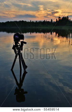 Camera On A Tripod Standing In The Lake. Sunset On The Lake.
