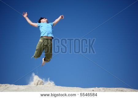 Boy Jumps On Sand With  Lifted Hands
