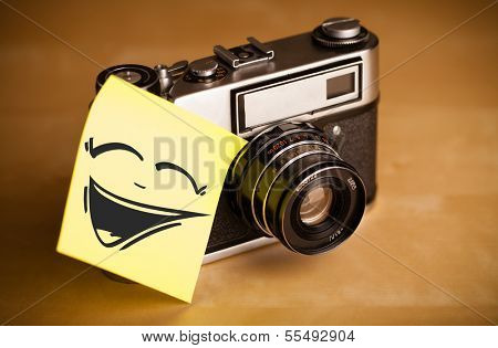 Drawn smiley face on a note stuck on a photo camera