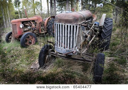 Two Old Rusty Tractor In The Forest