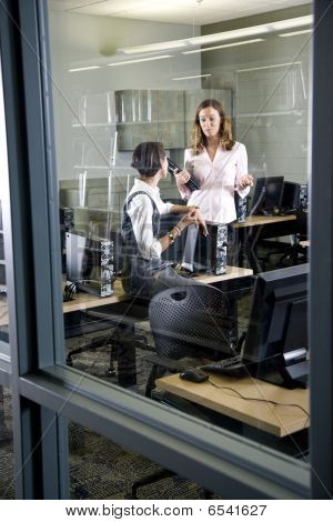 Two young women conversing in computer lab