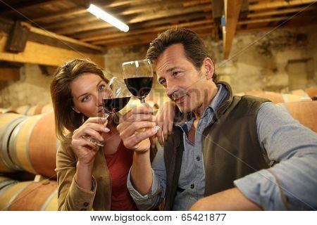 Oenologists in wine cellar tasting red wine