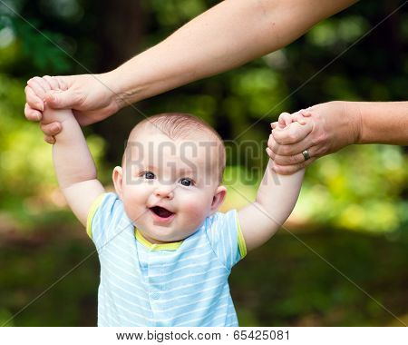 Happy Baby Boy Learning To Walk On Grass Outdoors