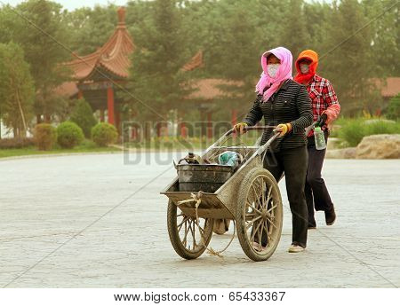 Inchuan, Inner Mongolia - Jul 6, 2011: Chinese Women Walking On The Street During A Sandstorm. In Re