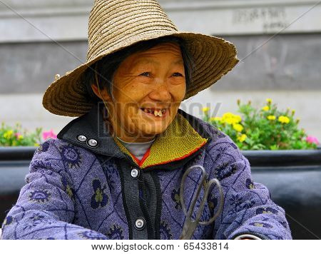 Wudanshan, China - Oct 31, 2007: Smiling Elderly Chinese Woman In A Straw Hat. In Recent Years, The