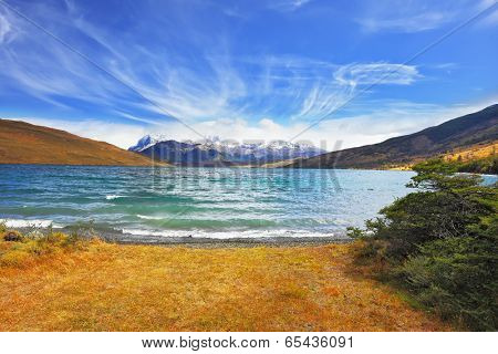 Lake in the high valley of the Patagonian Andes. The sharp strong wind drives the waves with white foam