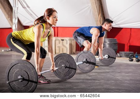Two Hispanic people lifting weights as part of the workout of the day in a  gym poster