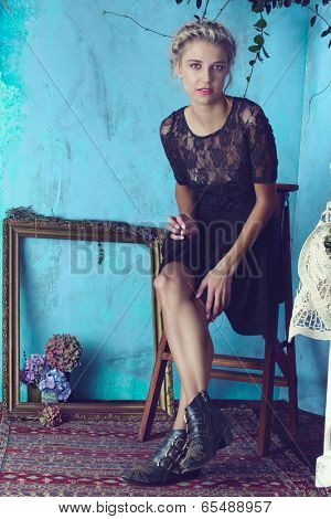 Beautiful blond woman with braid hairstyle and natural makeup. Wearing lace black dress and boots. Against grunge blue background