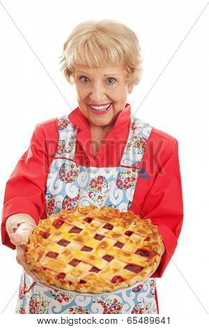 Sweet retro style grandmother holding a delicious home baked cherry pie with lattice top crust.  Isolated on white.