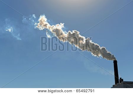 Industrial smokestack billowing smoke into atmosphere