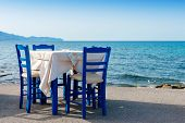 Table and chairs in sidewalk cafe at Kissamos Crete Greece poster