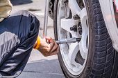 Mechanic technician worker replacing wheel vehicle of automobile at repair service station poster