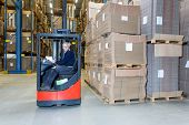 Reach truck forklift driving past an isle in a warehouse at speed. A panned image, with stock and cardboard boxes in the shelves of the storage racks. Conceptual image about internal logistics poster