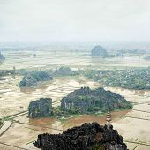 Amazing panorama view of the rice fields limestone rocks and mountaintop Pagoda from Hang Mua Temple at the early rainy morning. Ninh Binh Vietnam. Travel landscapes and destinations background poster