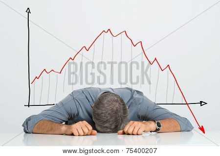 Depressed Businessman Leaning His Head Below a Bad Stock Market Chart