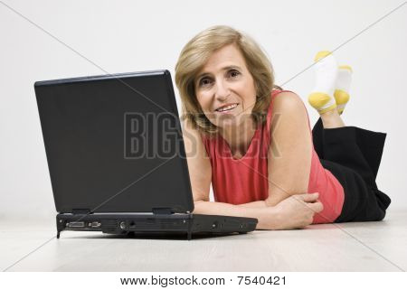 Mature Woman Lying On Floor Using Laptop