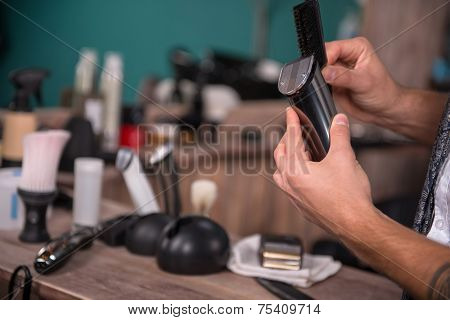 hairdresser  cleaning gray hair clipper  with brush  in  professional  hairdressing salon   with selective focus poster