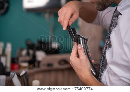 poster of hairdresser  cleaning gray hair clipper  with brush  in  professional  hairdressing salon   with selective focus