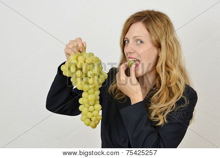 Young blonde girl eating a bunch of grapes