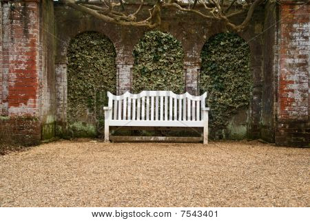 A Single White Bench  In Front Of An Ivy-covered Brick Wall At The End Of A Gravel Pathway