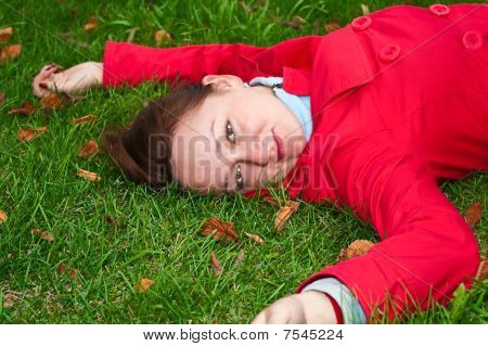 Woman With The Yellow Leaf Lies On The Green Grass Meadow