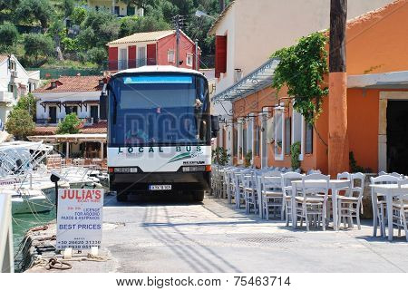 PAXOS, GREECE - JUNE 14, 2014: The local island bus negotiates the narrow seafront road at Loggos on the Greek island of Paxos. Taverna diners have to vacate their seats to allow the bus to pass.