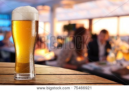 Photo of cold beer glass on the bar table.