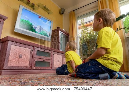 children sit in front of a tv and watch a children's show on.