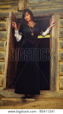beautiful young woman with dark hair in a black velvet historical dress is standing at the door