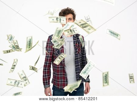 Casual man throwing Money Into Air over gray background