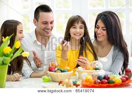 Happy family have fun with Easter eggs, together on holiday