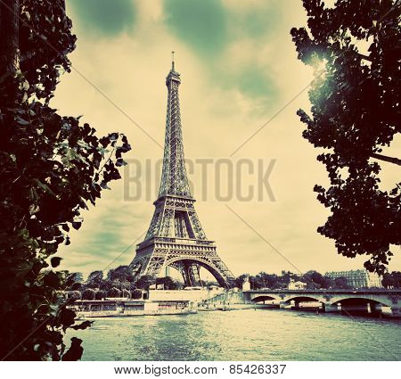 Eiffel Tower and Seine River, Paris, France. Unique perspective from behind trees next to tourist boats. Vintage