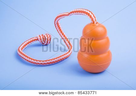 An orange tug type rubber dog toy on a blue background.
